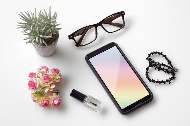 トップビュー女性携帯電話のモックアップ。女性のデスクトップワークスペースのオーバーヘッドショット。
