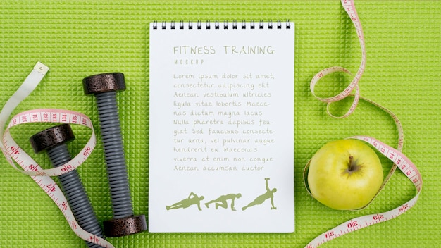 Top view of fitness notebook with apple and measuring tape