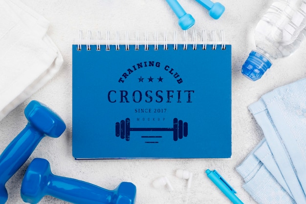 Top view of fitness notebook with jumping rope and weights