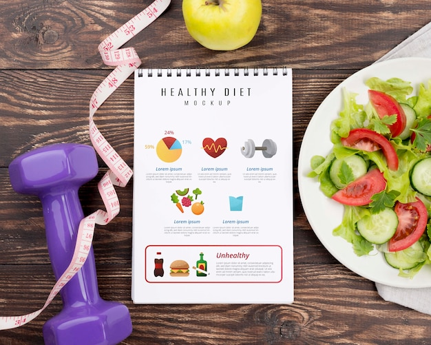 Top view of fitness notebook with plate of salad and measuring tape