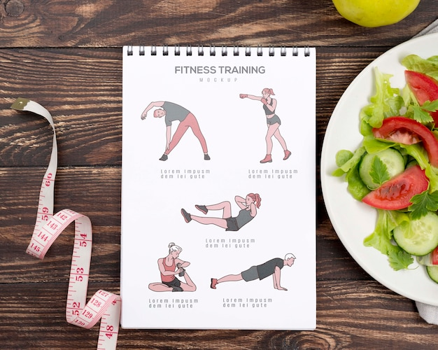 Top view of fitness notebook with salad and measuring tape