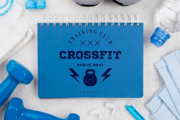Top view of fitness notebook with weights and jumping rope