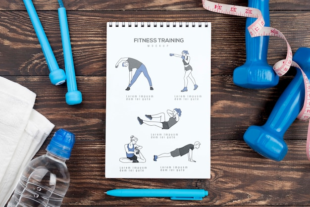 Top view of fitness notebook with weights and water bottle