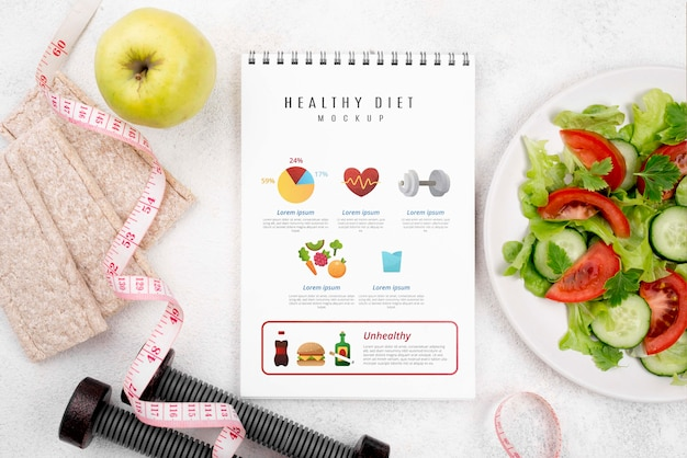 Top view of fitness notebook with with salad and weights