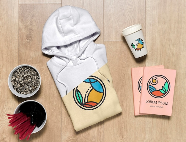 Top view folded hoodie mock-up with notebooks, cup and sunflower seeds