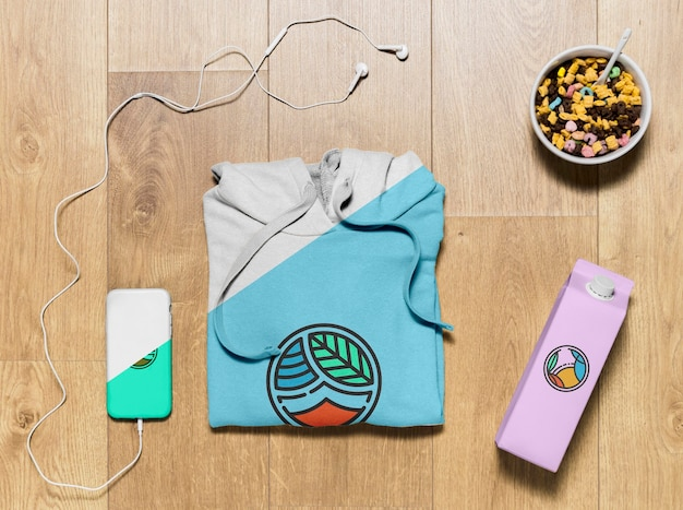 Top view folded hoodie mock-up with phone case, bottle and snack