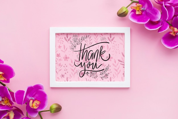 Top view of frame mock-up and flowers on pink background