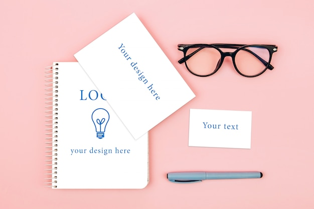 Top view of glasses and notebook on pink background, mockup