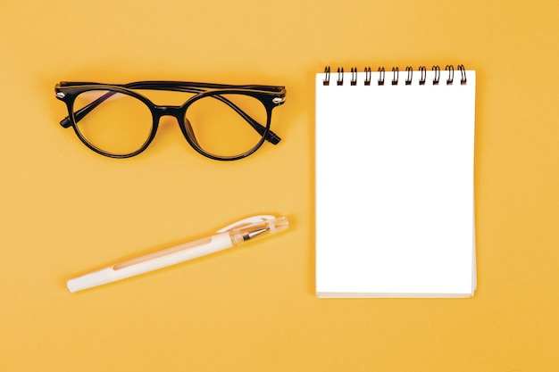 Top view of glasses and notebook on a yellow background, mockup, scene creator