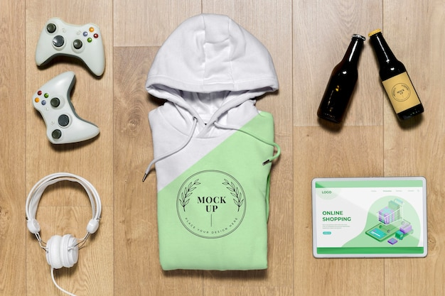 Top view green folded hoodie mock-up with gadgets and bottles