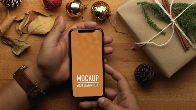 Top view of hand holding smartphone mockup and christmas decorations