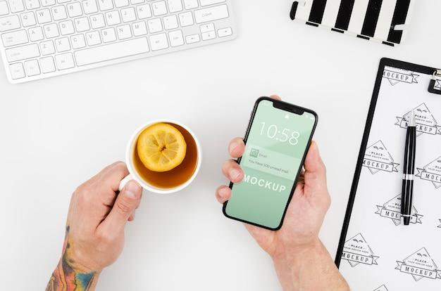 Вид сверху руки, держащие макет смартфона и чай