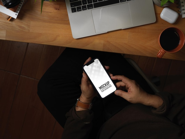 Top view of hands using smartphone mockup