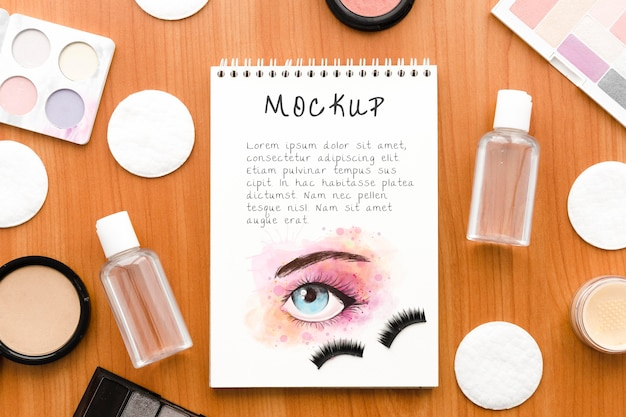 Top view make-up cosmetics arrangement with notepad mock-up