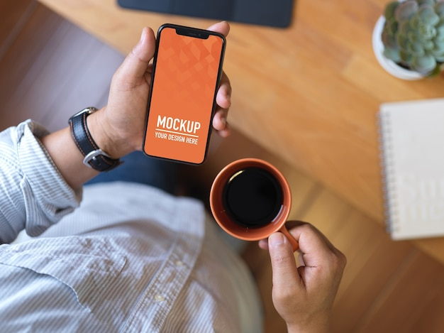 Top view of male hand holding smartphone mockup and coffee cup