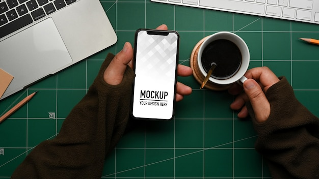 Top view of male hand holding smartphone mockup on workspace