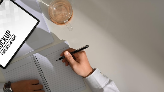 Top view of male hand writing on blank notebook while working with digital tablet mockup