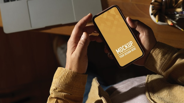 Top view of male hands using smartphone mockup Premium Psd