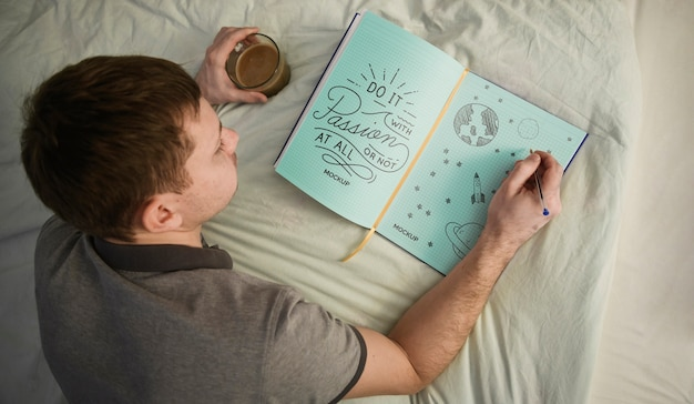 Top view of man writing in notebook on bed
