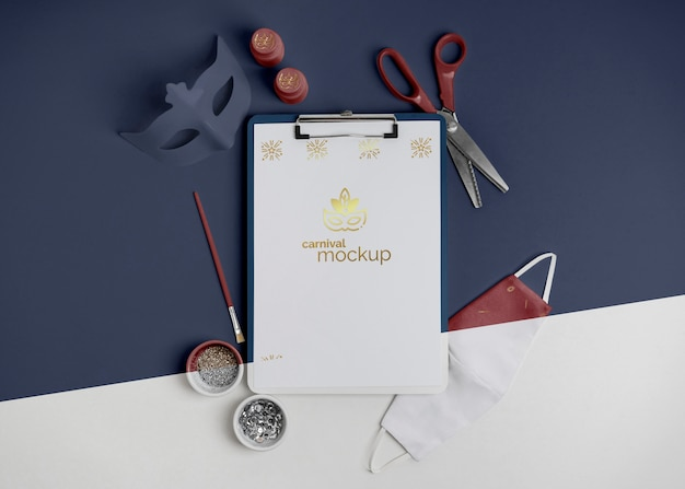 Top view of minimalistic carnival invitation with clipboard and scissors