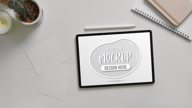 Top view of mock up digital tablet on white desk with notebooks Premium Psd