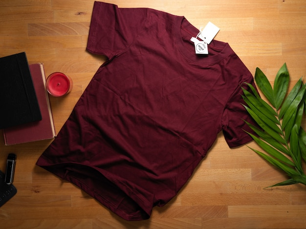 Top view of mock up red t-shirt with mock up price tag on wooden table with decorations