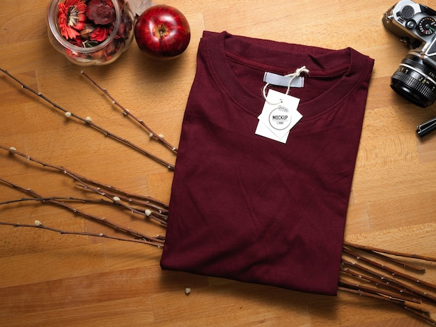 Top view of mock up red t-shirt with price tag on wooden table with decorations