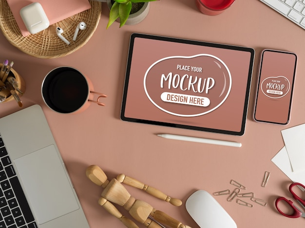 Top view of mock up tablet and smartphone on pink table with accessories and supplies