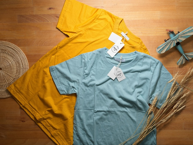 Top view of mock up yellow and blue t-shirt with mock up price tags on wooden table