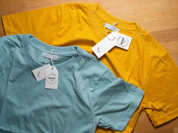 Top view of mock up yellow and blue t-shirts with price tags on wooden table