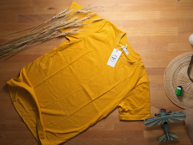 Top view of mock up yellow t-shirt with mock up price tag on wooden table with decorations