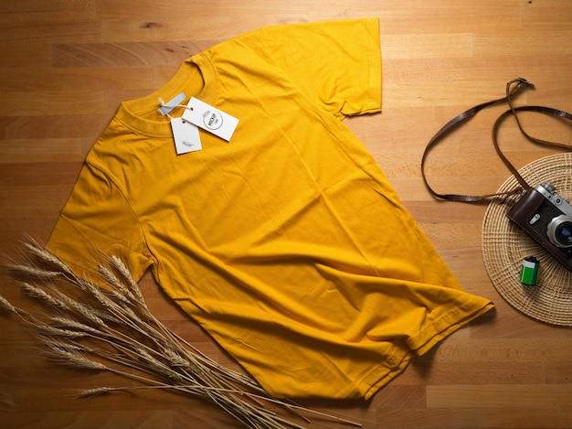 Top view of mock up yellow t-shirt with mock up price tag on wooden table