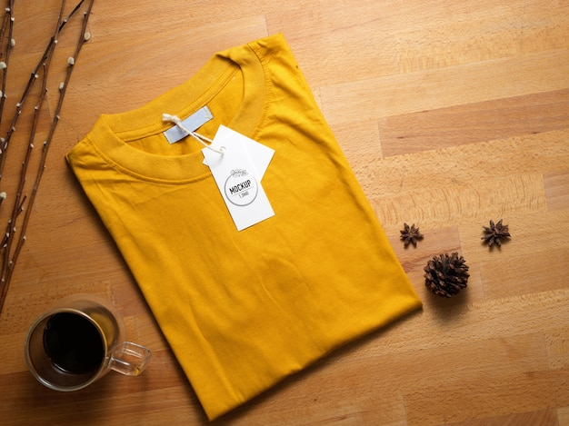 Top view of mock up yellow t-shirt with price tag on wooden table with coffee cup