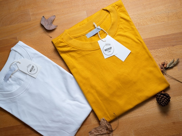 Top view of mock up yellow and white t-shirt with price tags on wooden table
