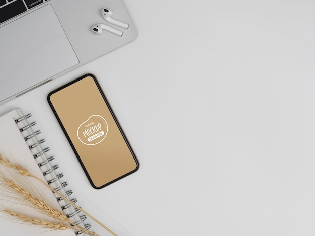 Top view of mockup smartphone on white worktable with laptop, earphone and copy space