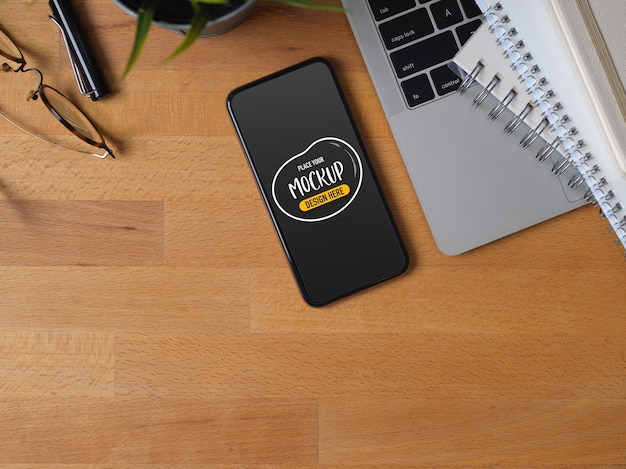 Top view of mockup of smartphone with laptop, stationer and glasses