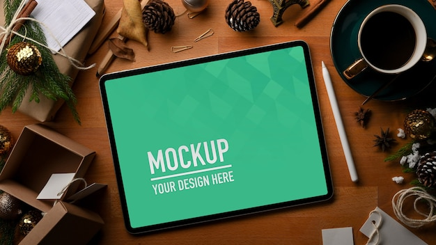 Top view of mockup tablet with coffee cup and christmas decorations Premium Psd