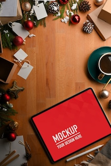 Top view of mockup tablet with coffee cup and christmas decorations