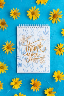 Top view of notebook and flowers on blue background