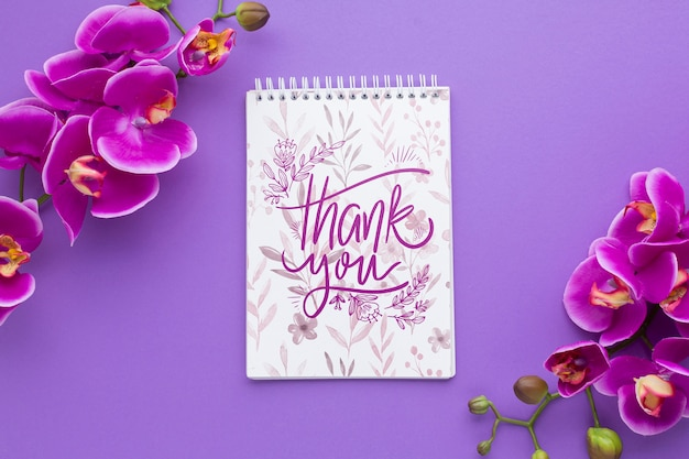 Top view of notebook and flowers on purple background