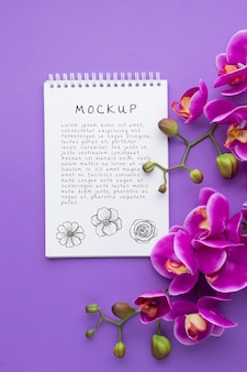 Top view of notebook mock-up with orchid