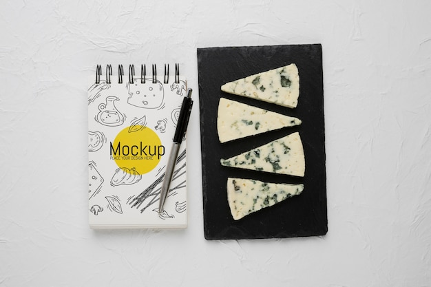 Top view of notebook and pen with moldy cheese