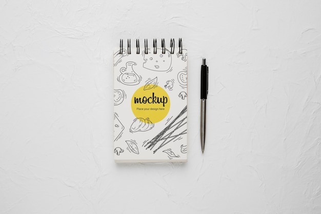 Top view of notebook with cheese design and pen
