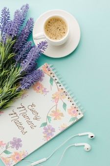 Top view of notebook with coffee and spring flowers