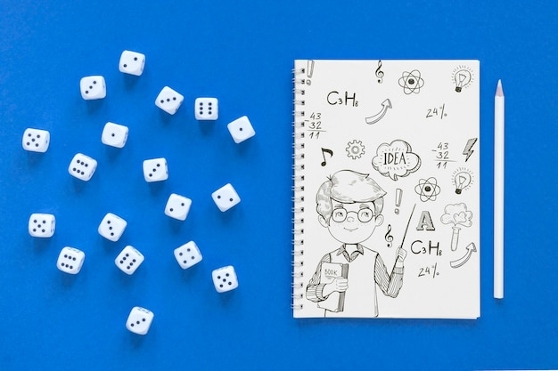 Top view of notebook with dice and pencil