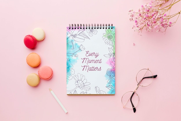Top view of notebook with flowers and macarons