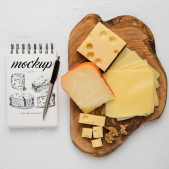 Top view of notebook with pen and variety of cheese