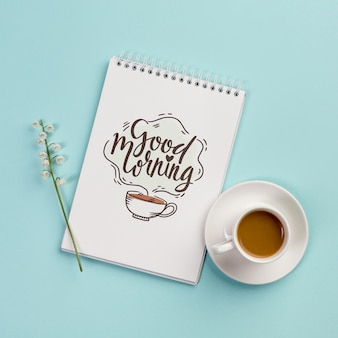 Top view notebook with positive message and coffee