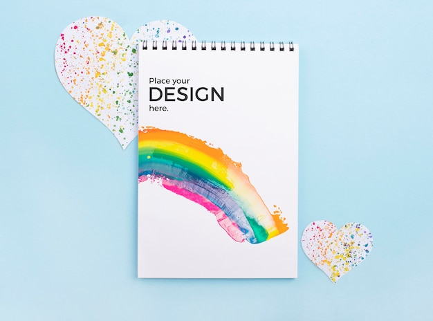 Top view of notebook with rainbow and heart