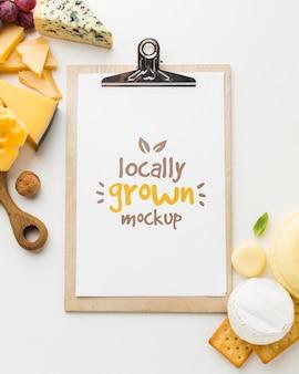 Mock-up di blocco note con vista dall'alto con assortimento di formaggi coltivati localmente